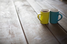 Yellow and blue cups of coffee on a wooden table.