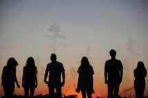 silhouettes of people standing outdoors at sunset