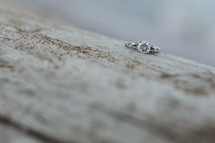 engagement ring on concrete with sand