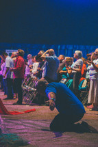 kneeling and prayer and  praising God at a worship service