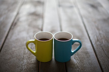 Yellow and blue cups filled with coffee and on a wooden table.