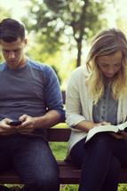 a couple sitting on a park bench, reading and texting