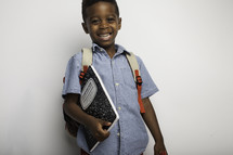 a boy with a book bag holding a composition notebook