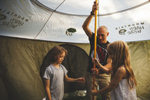 A family setting up a tent.