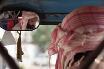 man driving a car with a headdress