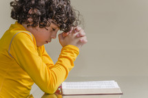 boy child in prayer in front of a Bible