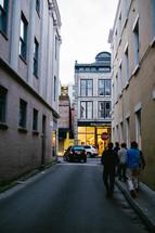 Young men walking down an alley toward retail shops.
