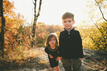 brother and sister standing outdoors