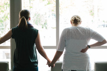 women holding hands in prayer standing in front of a window