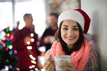 A smiling woman wearing a santa hat and holding a cup of coffee