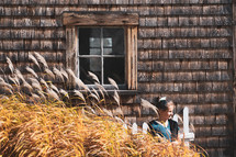a girl standing outdoors behind wheat