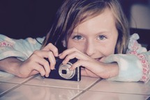 a little girl holding a camera