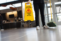 man with a dust mop and wet floor sign