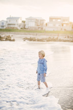 blonde boy child standing in the sand on a beach
