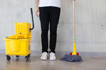a man standing with a mop and mop bucket