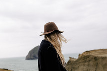 A blonde woman in a hat stands near the ocean.