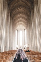 a woman standing in a large cathedral with tall arched ceiling and wooden chairs