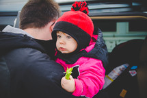 father holding his toddler girl holding a celery stick
