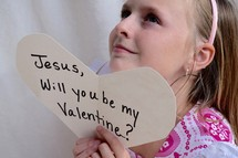 A little girl holding up a Valentine's day card for Jesus