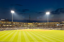 fans and stadium lights at a baseball diamond