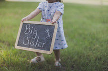 "Girl holding a ""big sister"" chalkboard sign outside."