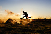 man running and jumping with a smoke flare