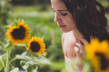 A young woman standing among sunflowers.
