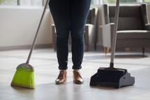 a woman with a broom and dust pan