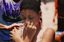 A girl holding her nose as she is baptized.