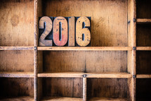 "Wooden letters spelling ""2016"" on a wooden bookshelf."