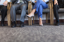 legs of a man and woman in chairs at a meeting