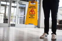 man in a lobby putting down a wet floor sign