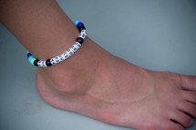 He anchors me bracelet around a child's ankle