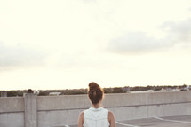 Back of a woman standing on a rooftop.