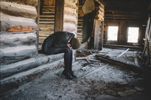 A woman bent over in grief in an abandoned log house.