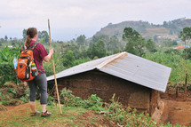 a woman with a backpack standing with a walking stick near a humble house