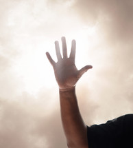 raised hand in a smoky sky