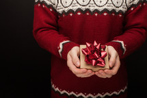a man in a sweater holding a Christmas gift box