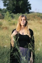 a woman in a black cloak standing outdoors in tall grasses