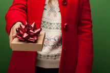 a woman in a red coat giving a gift at Christmas