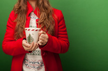 a woman in a red peacoat holding a mug
