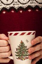 a man holding a Christmas mug