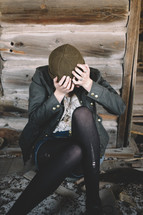 A woman sits with head in hands in an abandoned log house.