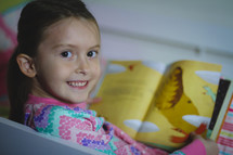 Smiling girl in pajamas reading the children's picture Bible at bedtime.