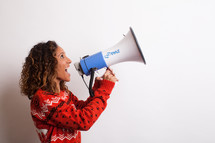 woman in an ugly Christmas sweater yelling into a megaphone