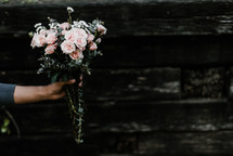 a woman holding out a bouquet of flowers