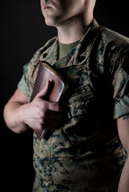 marine holding a Bible against his chest