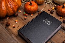 Holy Bible on a wood table surrounded by pumpkins