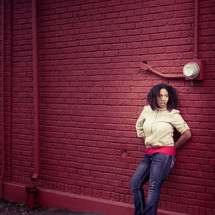 African American woman leaning against a red brick wall