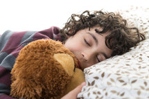 a child sleeping holding a teddy bear